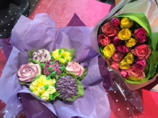 cupcake bouquet positioned next to a flower bouquet