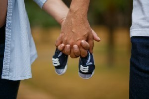2 people holding hands with baby shoes in the middle