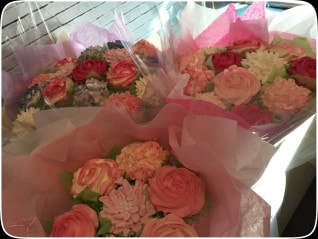 12 cupcakes in a bouquet to look like a flower bouquet in pinks reds and white colours