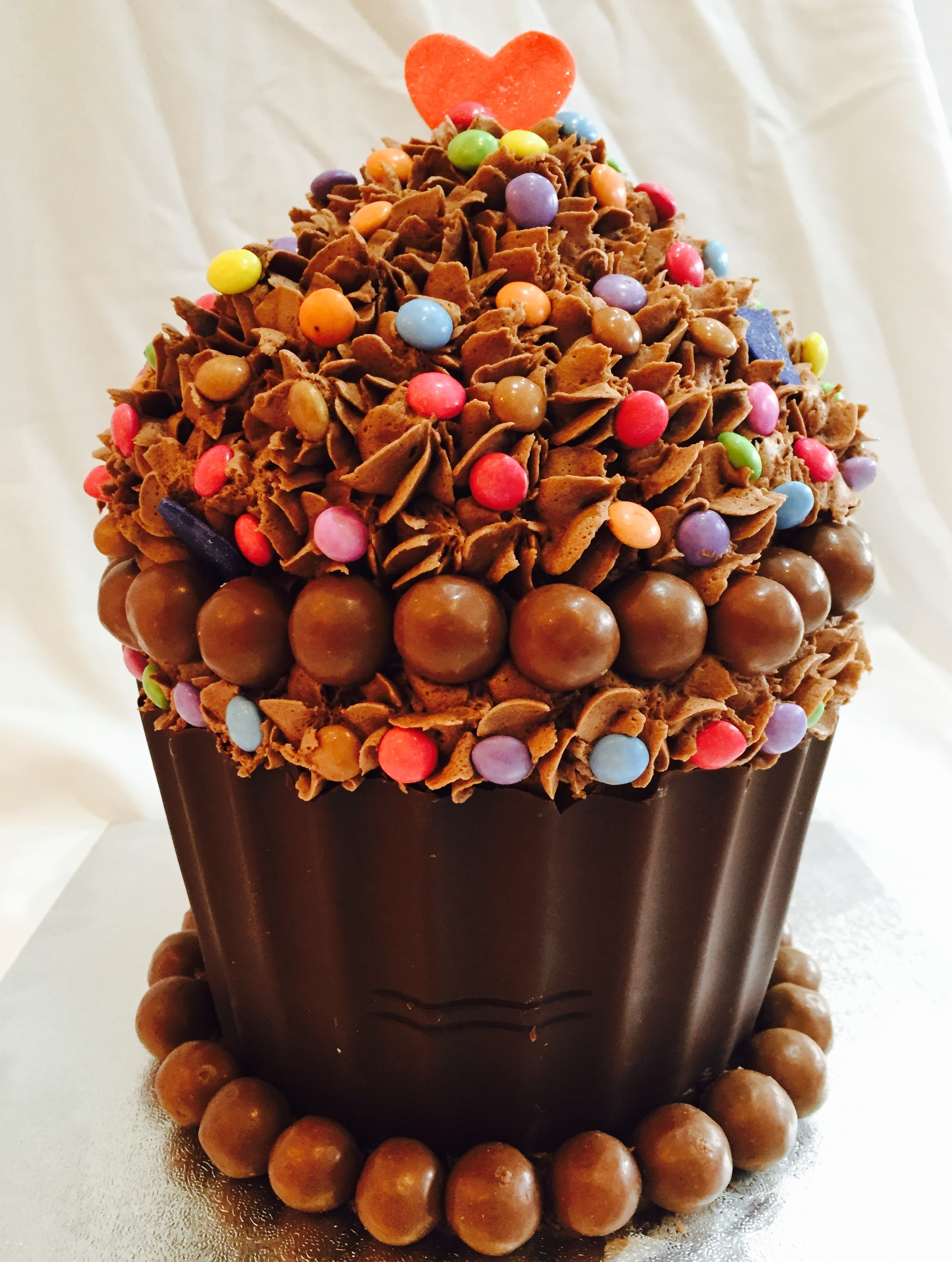 Chocolate giant cupcake with sponge cake and sweets as decoration
