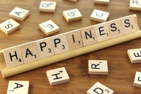 scrabble letters spelling out happiness