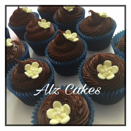 Chocolate cupcakes with chocolate buttercream and adorned with sugar flower primrose.
