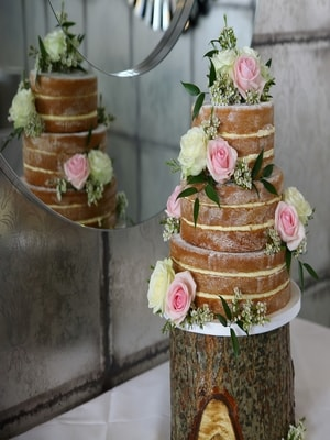 Wedding cake made of sponge cake three tiers with sugarcrafted flowers